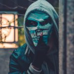 Dealing With The Imposter Syndrome - Second Image on Blog of a Man in a Mask with a silence Finger pointed to his face.